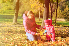 Mother and little daughter play in autumn fall Royalty Free Stock Image