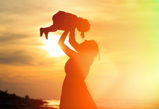 Mother and little daughter play at sunset Stock Photos