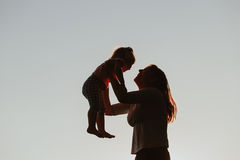Mother and little daughter play at sunset Royalty Free Stock Photo