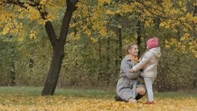 Mom hugs a little daughter in the autumn forest stock photo