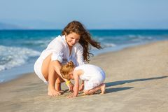 Mother and daughter playing on the beach Stock Images