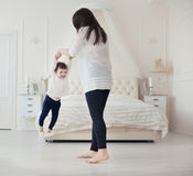 Mother and little daughter playing in the bedroom Royalty Free Stock Photo