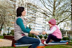 Mother with little daughter are playing at carousel Royalty Free Stock Photography