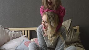 Mother and little daughter are playing and hugging on the bed. Happy motherhood. Slow motion stock video footage