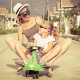 Mother and little daughter playing near a house at the day time. Stock Photography