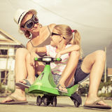 Mother and little daughter playing near a house at the day time. Royalty Free Stock Photos