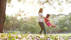 Mother and little daughter playing in a park. stock footage