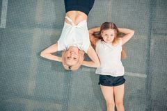 Mother and little daughter playing at playground and lying on trampoline royalty free stock photos
