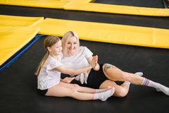 Mother and little girl playing at playground and lying on a trampoline stock images