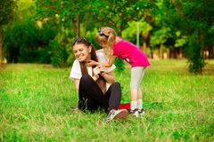 Mother and little daughter playing together in park. Outdoor Portrait of happy family. Happy Mother`s Day Joy. Mom and Baby royalty free stock image
