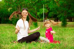 Mother and little daughter playing together in park. Outdoor Portrait of happy family. Happy Mother`s Day Joy. Mom and Baby stock photography
