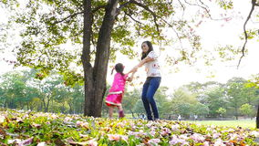 Mother and little daughter playing together in a park stock footage