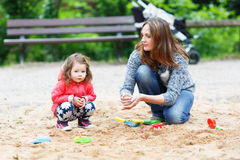 Mother and little daughter playing together on playground Stock Image