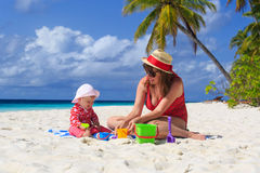 Mother and little daughter playing on tropical beach Royalty Free Stock Photos