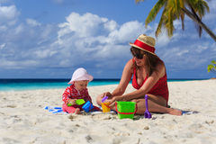 Mother and little daughter playing on tropical beach Royalty Free Stock Photo