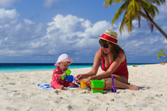 Mother and little daughter playing on tropical beach Stock Photo