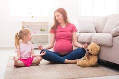 Mother and little daughter practicing yoga at home stock image