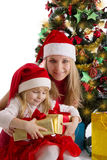 Mother and little daughter with presents under Christmas tree Stock Photos