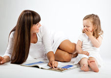 Mother  and little daughter reading book Stock Photo
