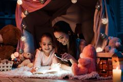 Mother and daughter are reading book with flashlight in pillow house late at night at home. Royalty Free Stock Image