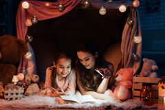 Mother and daughter are reading book with flashlight in pillow house late at night at home. Royalty Free Stock Photography