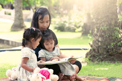 Mother and little daughter reading book together Stock Photos