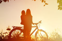 Mother and little daughter riding bike at sunset Stock Photos