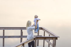 Mother and the little daughter are on the river jetty. Sunset. Fog. Royalty Free Stock Photography