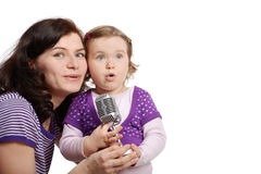 Mother with little daughter sing into microphone Royalty Free Stock Photos
