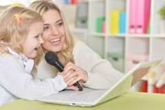 Mother with little daughter singing songs. With laptop stock photo