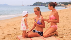 Mother little daughter sit on mat eat roll woman brings beverage stock video footage