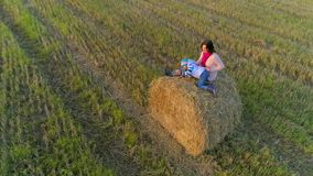 Mother with daughter sit on the straw stack on the rustic field in the sunset. A mother with a little daughter sit on the straw stack on the rustic field at the stock footage