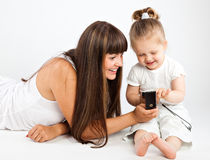 Mother  and little daughter speaking by phone. Gray background Stock Image