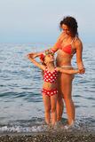 Mother and little daughter standing on beach. Young mother and little daughter standing on beach.  on head of girl is garland of Hawaiian flowers Stock Photography
