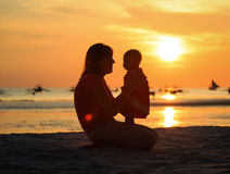 Mother and little daughter on sunset beach Stock Photo
