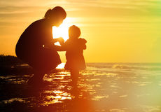 Mother and little daughter on sunset beach Stock Photography