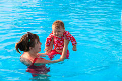 Mother and little daughter swim on vacation Stock Photo