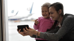 Mother with little daughter taking a selfie at airport. Young mother with little daughter taking a selfie at airport with airplane on the background stock video footage