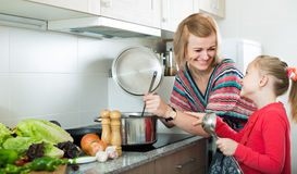 Mother and little daughter tasting soup together Royalty Free Stock Images