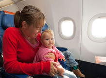 Mother and little daughter travel by plane stock photo