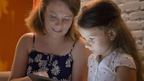 Mother with little daughter typing on tablet, sitting on couch at home, family concept indoors stock video