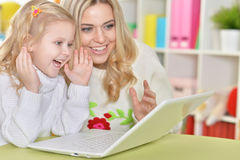 Mother with little daughter using laptop Stock Photography