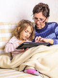 Mother and little daughter using tablet device Stock Photos