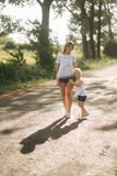 Mother and little daughter walk though the alley and hold each others hands. Shadow on the road stock photo