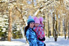 Mother with a little daughter on a walk in the woods on a snowy winter royalty free stock photography