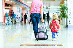 Mother and little daughter walking in the airport Stock Images