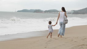 Mother with little daughter walking along the sea in bad weather stock video footage