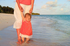 Mother and little daughter walking on beach Royalty Free Stock Image