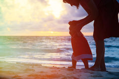 Mother and little daughter walking on beach at Stock Images