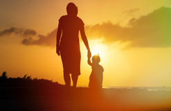 Mother and little daughter walking on beach at Stock Photo